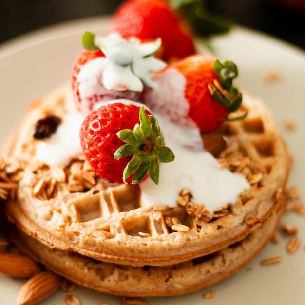 Close up waffles with strawberries and yogurt Free Photo