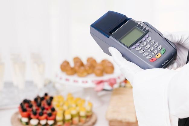 Крупным планом официант держит телефон Бесплатные Фотографии