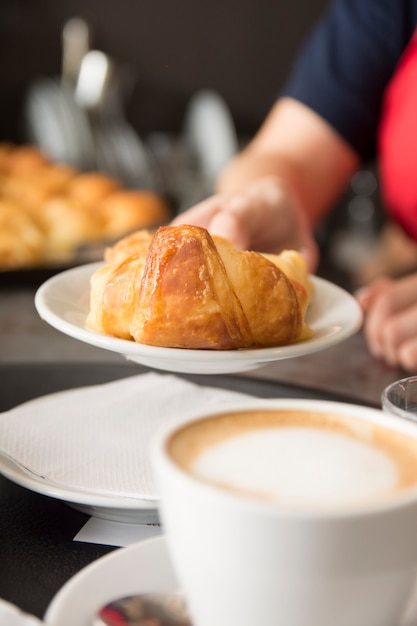 Close-up of waitress's hand offering baked croissant Free Photo