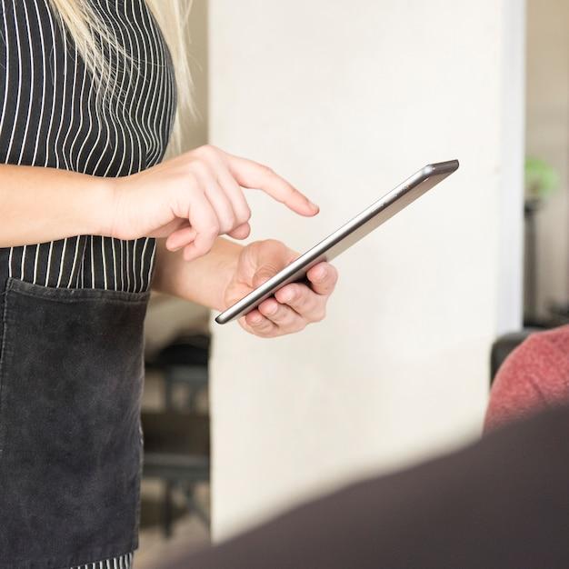 Close-up of waitress using digital tablet Free Photo