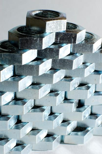 서로 옆에 벌집 형태의 수많은 크롬 금속 너트의 근접 벽 프리미엄 사진