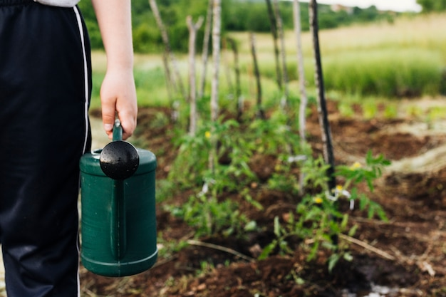 Close up watering can held in hand Free Photo
