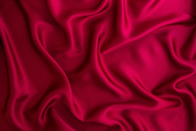 Close up wave red silk or satin fabric background Premium Photo