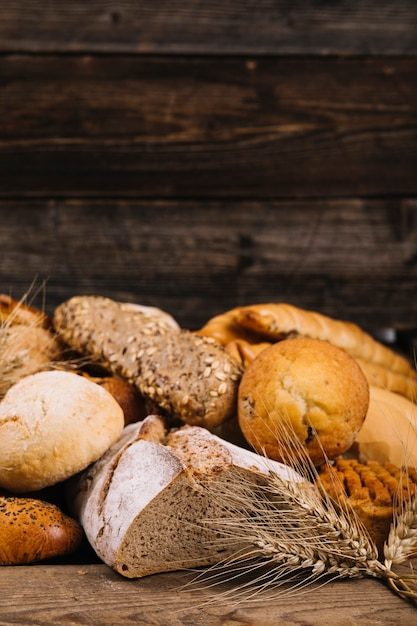 Close-up of wheat crop in front of baked bread on wooden table Free Photo