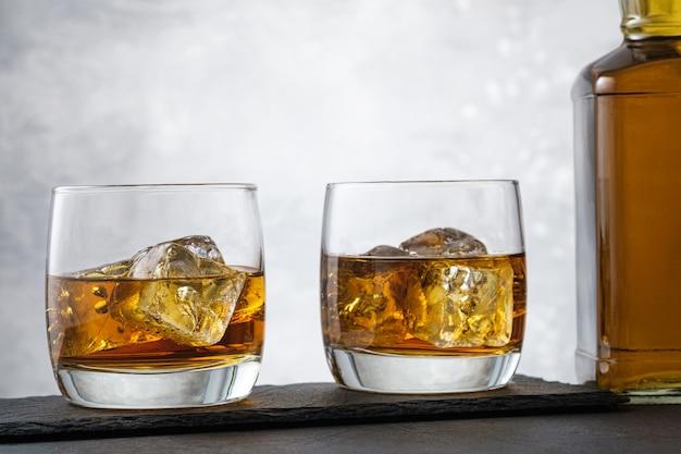 Крупный план виски с кубиками льда и бутылкой алкогольного напитка на сером фоне Premium Фотографии