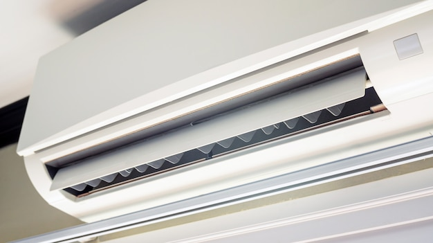 Close up of a white air conditioner in a room.