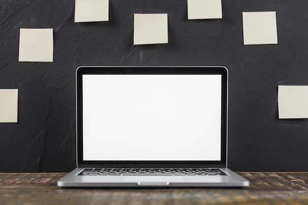 Close-up of a white blank screen laptop on wooden table Free Photo