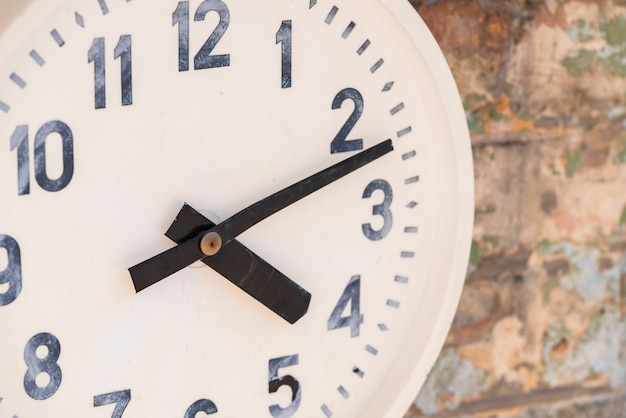 Close-up of a white clock on weathered wall Free Photo