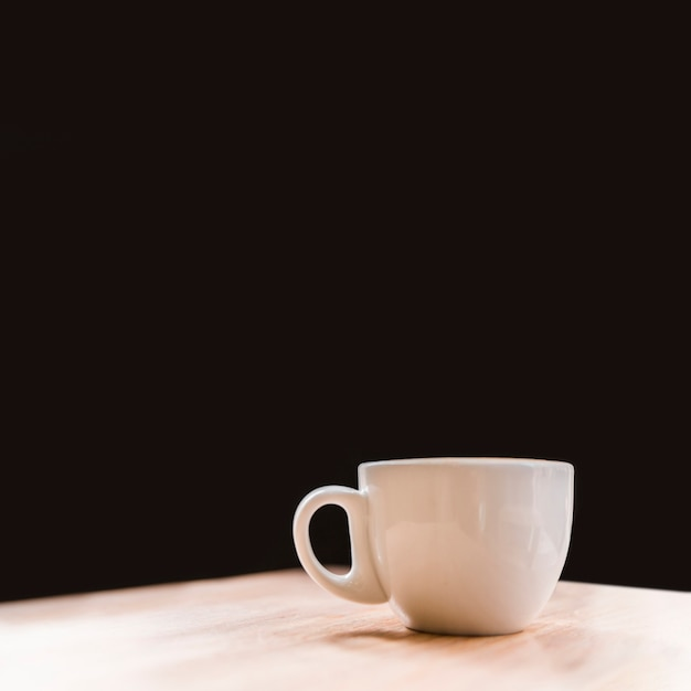Close-up of white coffee cup on desk over black backdrop Free Photo