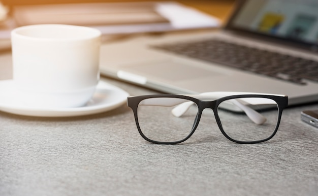 Close-up of white coffee cup and eyeglasses in front of laptop on gray background Free Photo