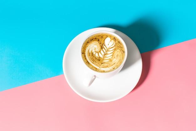 Close up white coffee cup with on blue and pink table, white cup of black coffee isolated on blue and pink table Premium Photo