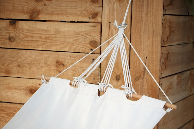 Close-up of a white hammock made of natural fabric on a wooden base Premium Photo
