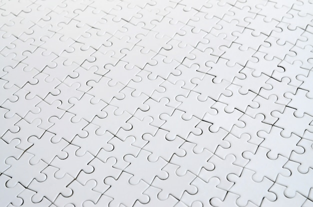Close up of a white jigsaw puzzle in assembled state in perspective Premium Photo