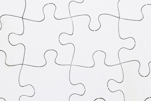 Close-up of white jigsaw puzzle grid background Free Photo