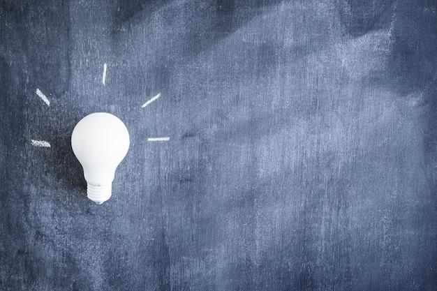 Close-up of white light bulb on blackboard Free Photo