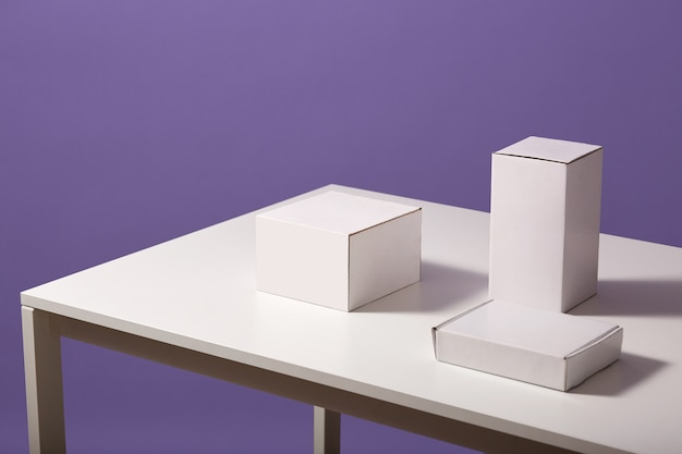 Close up of white paper carton boxes on table isolated over lilac, three blank cases on desk Free Photo