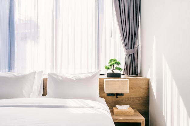 Close-up of white pillow on bed decoration with light lamp and green tree Premium Photo