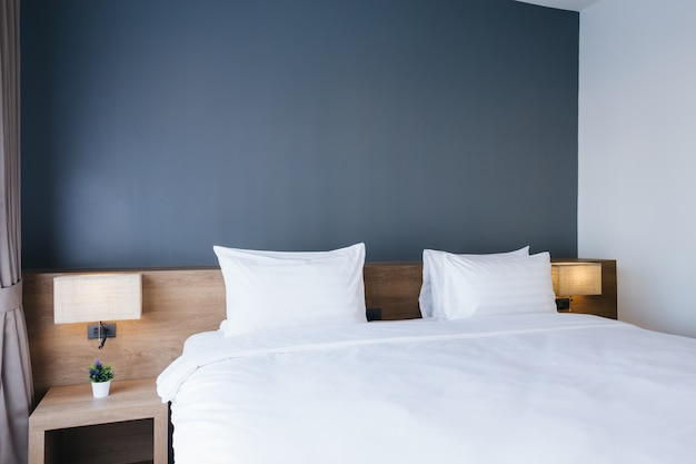 Close-up of white pillow on bed decoration with light lamp in hotel bedroom interior. Premium Photo