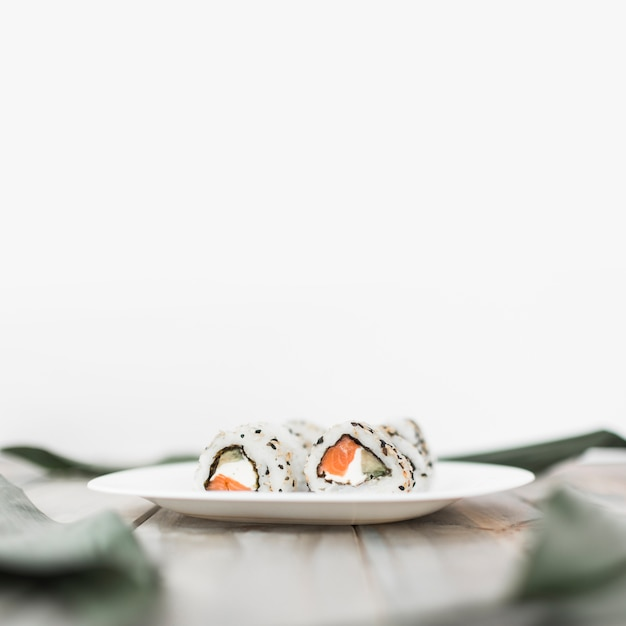 Close-up of white plate with sushi on wooden table against white backdrop Free Photo