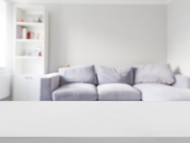 Close-up of white table in front of defocused sofa Free Photo