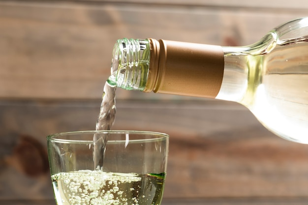 Close-up white wine poured in a glass Free Photo