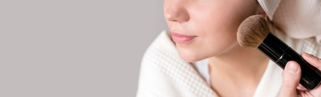 Close-up woman applying blush Free Photo