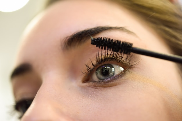 Close-up of woman applying mascara to her lashes Free Photo