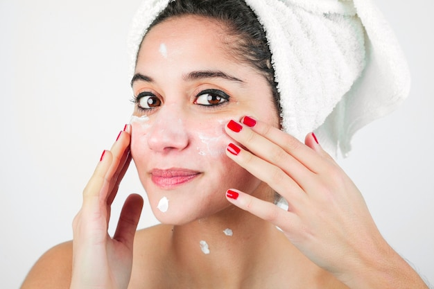 Close-up of woman applying moisturizer to her face Free Photo