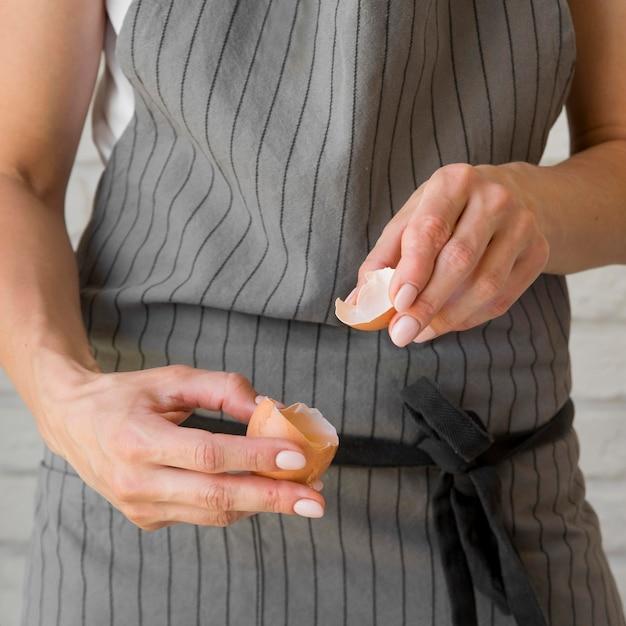 Donna del primo piano che rompe uovo Foto Gratuite