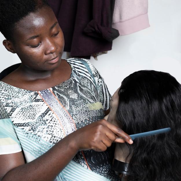 Close-up donna spazzolatura capelli bambola Foto Gratuite