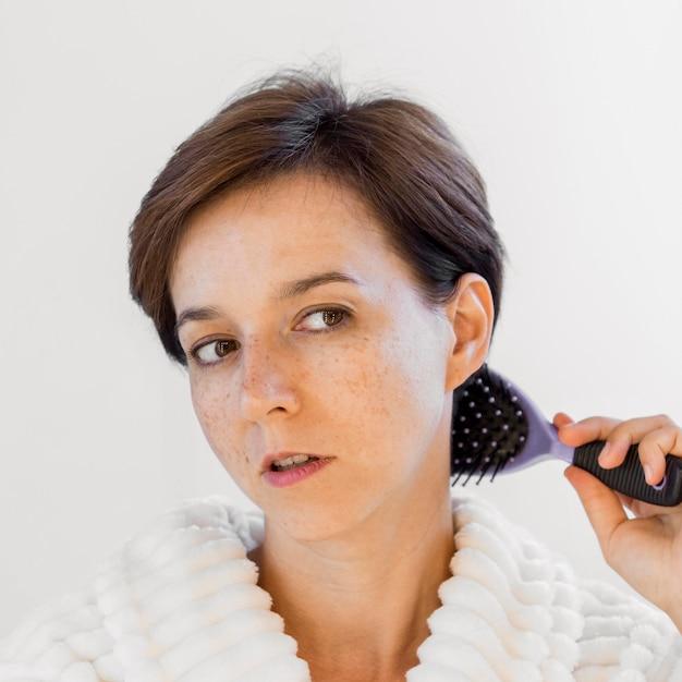 Женщина крупным планом, расчесывая волосы Бесплатные Фотографии