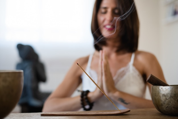 Close up of woman  burning an incense stick at her living room. woman meditating in buddhist atmosphere during isolation at home. Premium Photo
