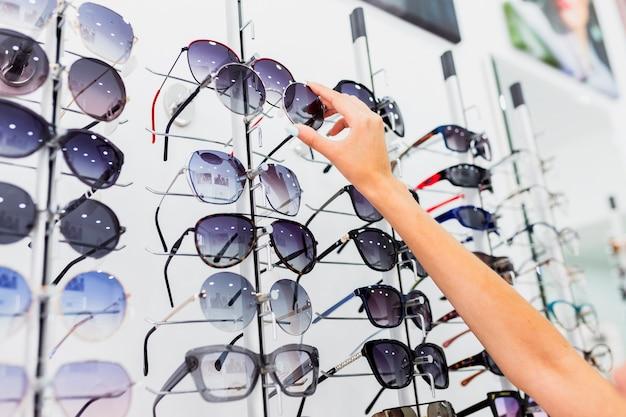 Close-up of woman checking sunglasses Free Photo