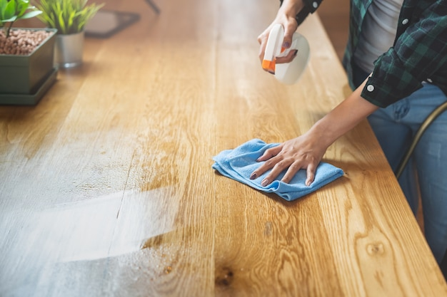 Close up woman cleaning kitchen using cleanser spray and cloth. Premium Photo