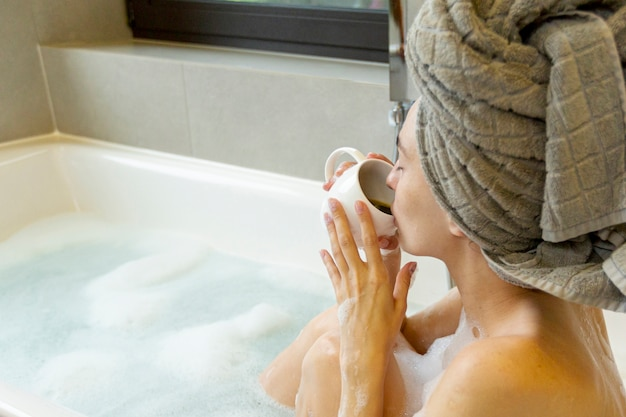 Close-up woman drinking coffee in the bathtub Free Photo