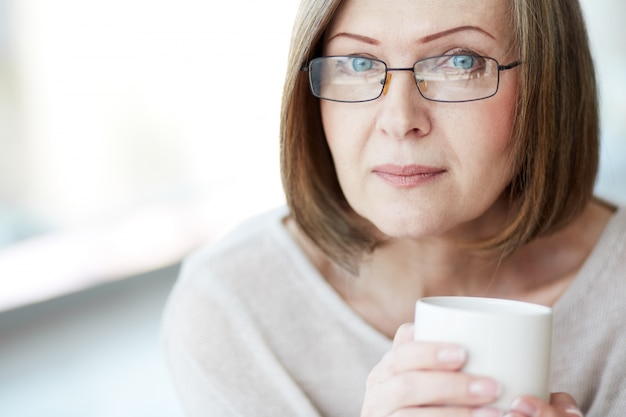 Close-up of woman drinking a hot drink Free Photo