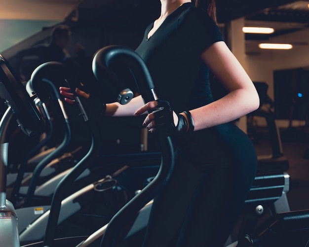 Close-up of a woman exercising on elliptical cardio machine Free Photo