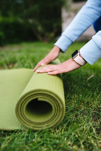 Primo piano di fitness rotolo pieghevole donna dopo aver lavorato nel parco Foto Gratuite