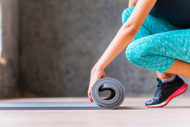 Close-up of a woman folding yoga mat Free Photo