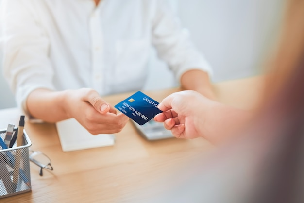 Close up of woman giving credit card payment from customer Premium Photo