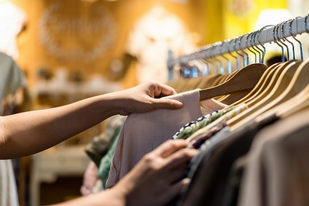 Close up of woman hand choosing thrift young and discount t-shirt clothes in store Premium Photo