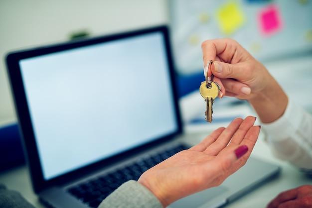 新しい女性の所有者にアパートのキーを与える女性の手を閉じます。 Premium写真