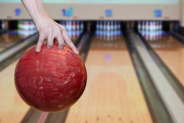 Close-up on woman hand holding bowling ball against bowling alley Premium Photo