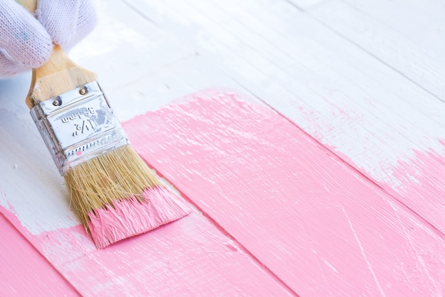 Close up woman hand holding brush painting pink color on a white wooden table. Premium Photo