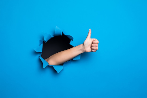Close up of woman hand with thumbs up gesture through blue hole in paper wall. Free Photo