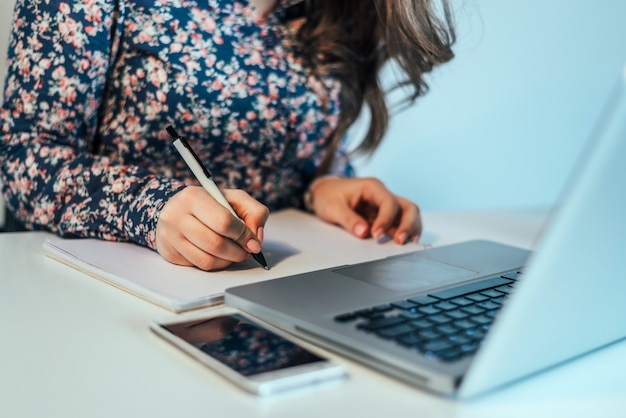Close up of a woman hand writing a contract with a laptop beside. Premium Photo