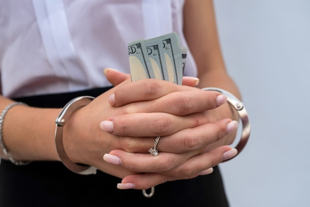 Close-up of woman hands in handcuffs holding dollar. bribe and corruption Premium Photo
