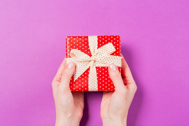 Close-up of woman hands holding gift present box on purple background. holiday valentine's day Premium Photo