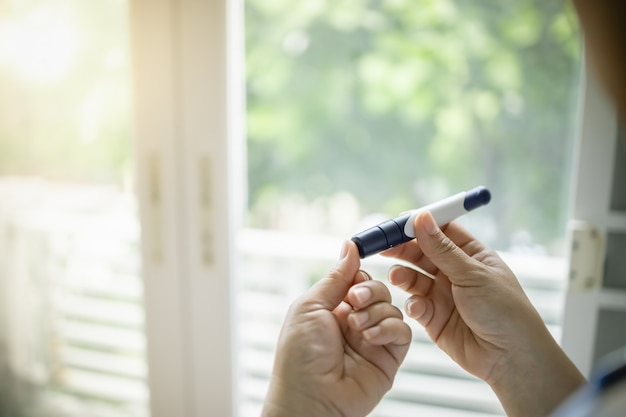Close up of woman hands using lancet on finger to check diabetes blood sugar level. Premium Photo