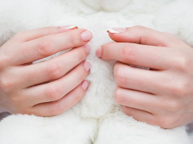 Chiuda sulle mani della donna con tessuto lanuginoso Foto Gratuite